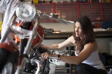 Mechanic repairing motorcycle in garage