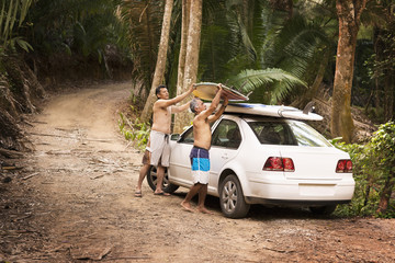 Hispanic men placing surfboards on roof of car in jungle