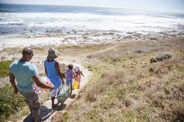 Mixed race family walking on path to beach