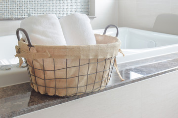 Towels in basket next to white bathtub in the bathroom