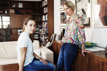 Serious mother and daughter in living room