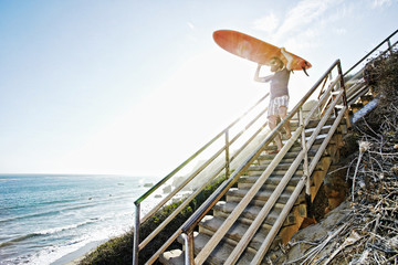 Caucasian man carrying surfboard on stairs at beach