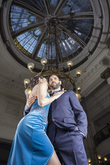 Tango Dancers Standing Below Cupola In Restaurant