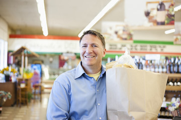Caucasian man carrying bag in grocery store