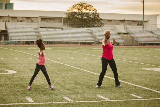 Grandmother and granddaughter exercising on football field