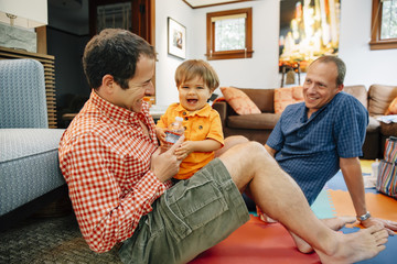 Gay fathers playing with baby son in living room