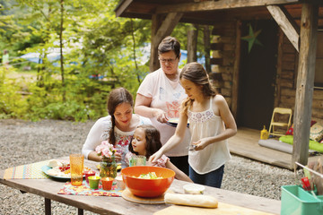 Three generations of women cooking outside cabin