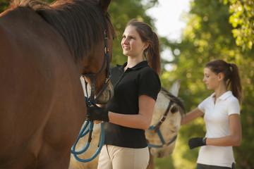Caucasian girls petting horses in rural landscape
