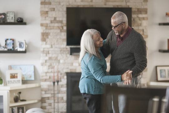 Older couple dancing in living room
