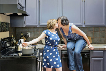 Lesbian couple cooking in kitchen