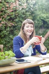 Mixed race businesswoman drinking coffee in backyard