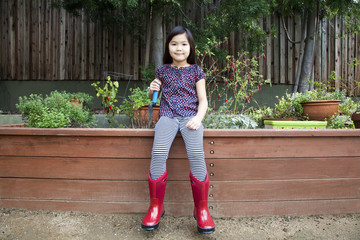 Mixed race girl wearing rain boots in backyard