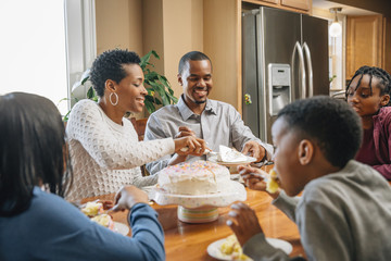 Black family eating cake at birthday party