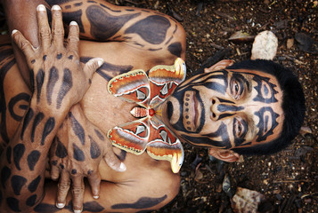 Hispanic man with painted body laying in dirt, Lago Izabal, Guatemala