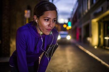 Hispanic runner resting on city street at night