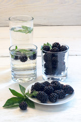 blackberry berries on a white plate with wood background