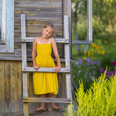 Cute little girl stands on a wooden ladder at the wall of a village house.