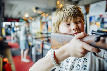 Boy aiming rifle in arcade shooting game