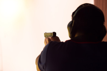 law enforcement aim pistol by two hand in academy shooting range in vintage color