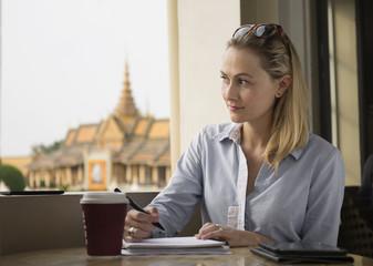 Caucasian businesswoman writing notes in cafe, Phnom Penh, Cambodia