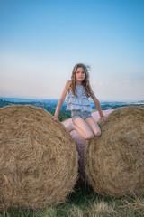 Fillette sur une meule de foin dans un champs