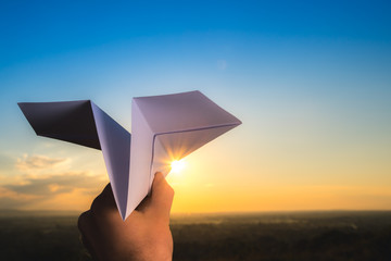 The hand hold paper airplane and launch on the background of bright sun and picturesque sunset