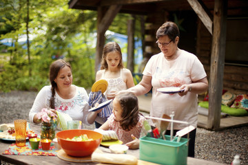 Three generations of Caucasian women cooking outside cabin