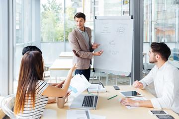 Confident businessman giving presentation using flipchart in office