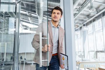 Businessman with clipboard entering the door in office