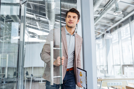 Businessman with clipboard entering the door in office