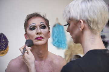 Stylist applying makeup to performer