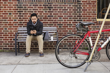 Hispanic man sitting on city bench using cell phone