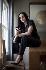 Caucasian businesswoman sitting in table using cell phone
