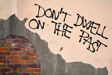 Do Not Dwell On The Past - handwritten graffiti sprayed on the wall, anarchist aesthetics - appeal to get over memories, nostalgia, retrospection. Motivation for living in present and future time