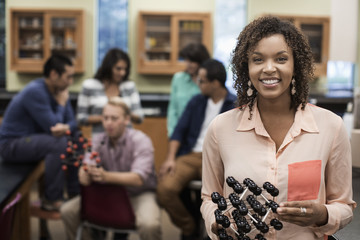 Mixed race student holding molecular model in lab classroom