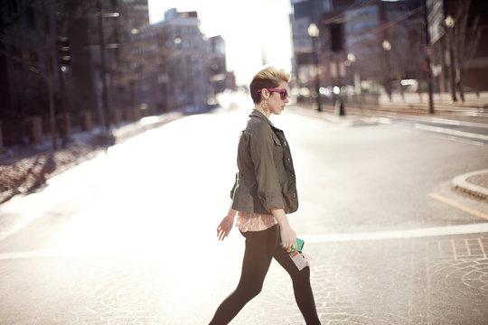 Beautiful young woman walking on city street