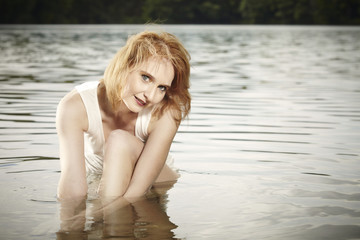 Tiny redhead beauty posing in summer water