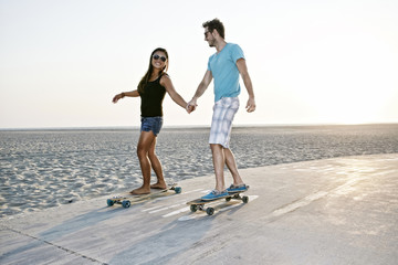 Couple skating on beach