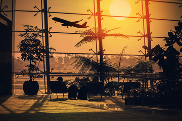 Tourists relax on the hammock in the lounge in the airport waiting to board a plane with a beautiful sunset and the plane background.