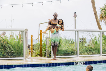 Father carrying daughter into swimming pool