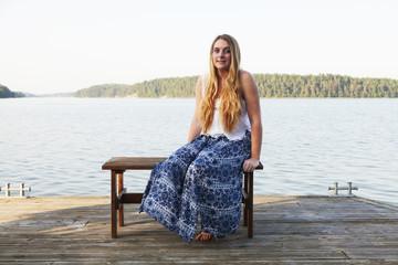 Caucasian teenage girl sitting on wooden dock at lake