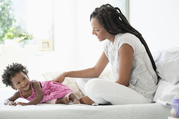 Black woman playing with baby daughter on bed