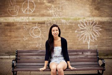 Woman sitting on urban bench near graffiti wall