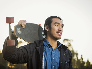 Chinese man carrying skateboard outdoors
