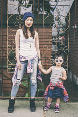 Korean mother and daughter holding hands on city street
