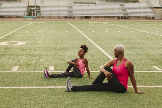 Grandmother and granddaughter stretching on football field