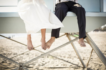 Asian bride and groom sitting on lifeguard hut on beach