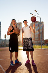 Two guys are standing on the basketball court with balls and looking at the camera. Spin the ball his finger.