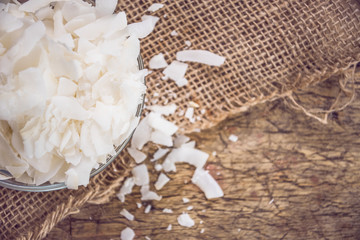 Dried coconut flakes on wooden background