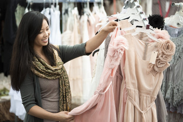 Chinese woman shopping for dresses at flea market